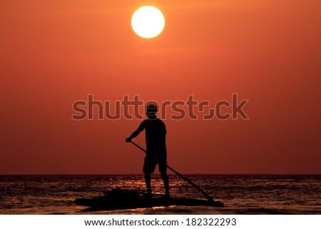 Man on paddle board at sunset - stock photo