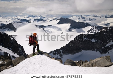 Man on peak of high Norwegian mountain.Galdhopiggen mountain. - stock photo