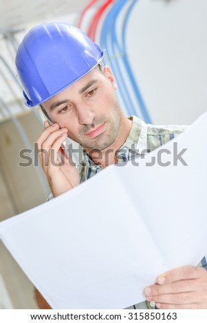 Man on phone looking at plans - stock photo