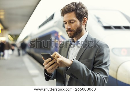 Man on platform station. Typing text message on mobile phone - stock photo