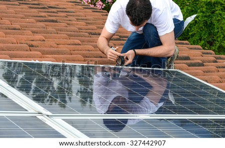 man on roof measuring for solar panel installation - stock photo