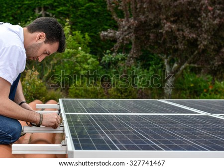 man on roof with curved tiles measuring for solar panel installation - stock photo