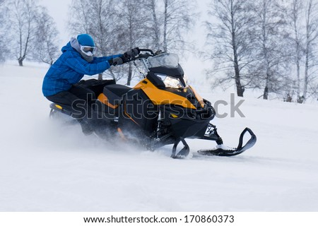 Man on snowmobile in winter mountain - stock photo