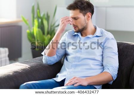 Man On Sofa Having Headache - stock photo