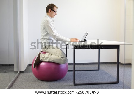 Man on stability ball working with tablet at desk in the office - stock photo
