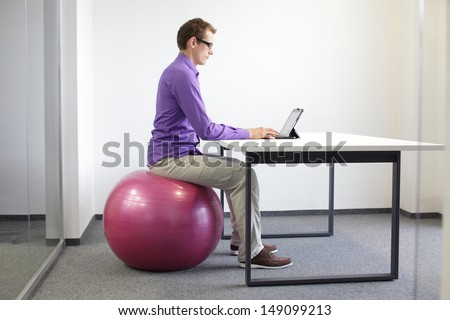man on stability ball working with tablet - correct sitting position at workstation   - stock photo