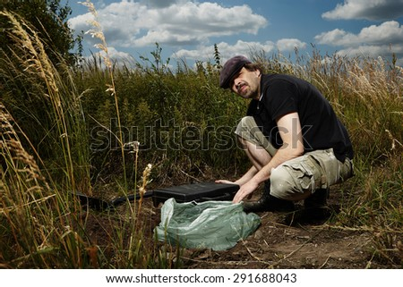 Man on summer meadow hiding suitcase full of drugs and weapon - stock photo