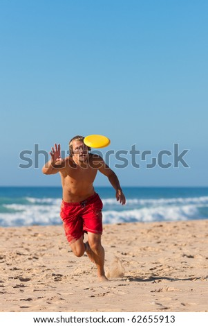 Man on the beach playing frisbee - stock photo