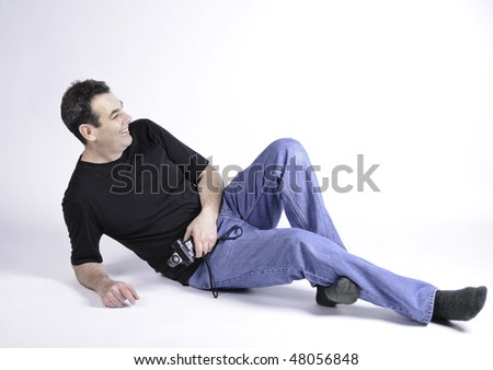 Man on the floor of studio laughing.He is wearing t-shirt and blue jeans with no shoes and holding a light meter. - stock photo