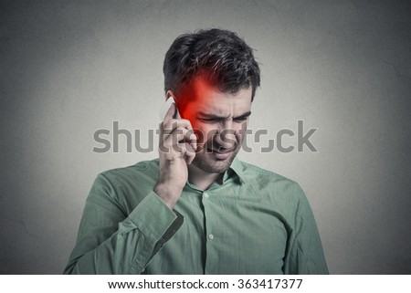 Man on the phone with headache. Upset unhappy guy talking on a phone isolated grey wall background. Negative human emotion face expression feeling life reaction. Cellular mobile radiation concept - stock photo