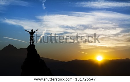 man on the top of a rock  meeting sun - stock photo