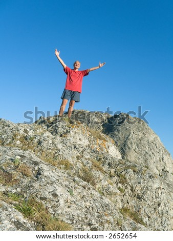 Man on the top of mountain - happiness and success - stock photo