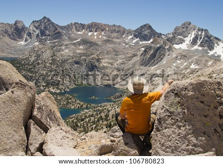 Man on top of Fin Dome enjoying the Rae Lakes Overlook in the Sierra Nevada mountains - stock photo