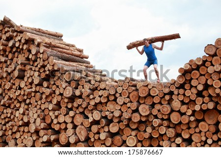 man on top of large pile of logs, lifting heavy log - training  - stock photo