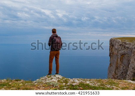 Man on top of mountain. Conceptual design.Young man with backpack standing with raised hands on top of a mountain and enjoying valley view. The idea of victory and the championship - stock photo