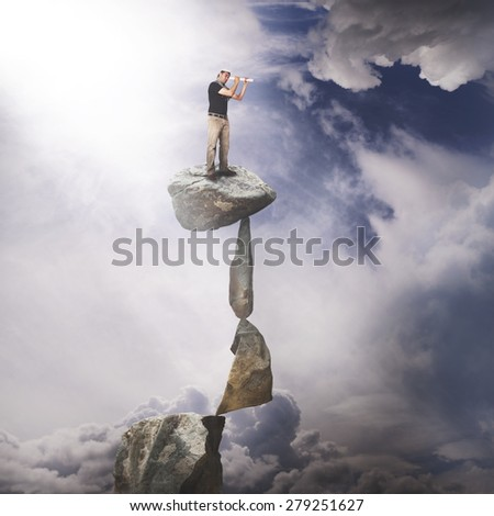Man on top of rocks looking ahead. Business vision concept - stock photo