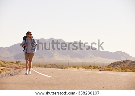 Man On Vacation Hitchhiking Along Country Road - stock photo