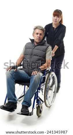 man on wheelchair with asian woman helping him - stock photo