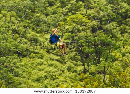 Man on Zipline over Lush Tropical Valley - stock photo