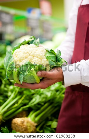 Man - only hands to be seen - in supermarket as shop assistant; he is carrying a cauliflower - stock photo