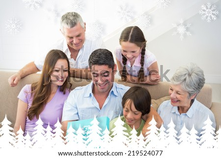 Man opening birthday present at home against fir tree forest and snowflakes - stock photo