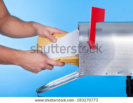 Man opening his mailbox to remove mail inside  close up of his hand on the open door against a blue sky - stock photo