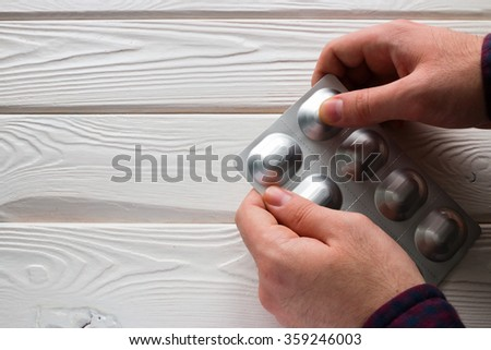 man opens a package of antibiotics tablets on a white background - stock photo