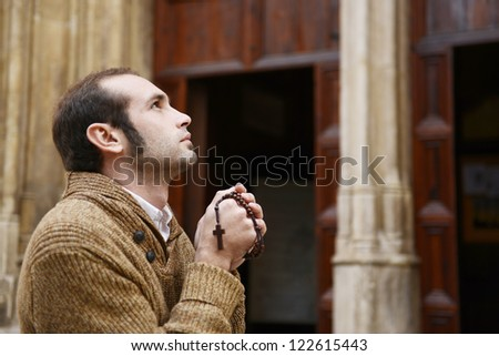 Man or monk praying in front of the church with rosario or prayer beads - stock photo