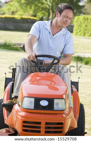 Man outdoors driving lawnmower - stock photo