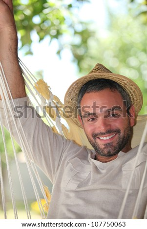 Man outdoors in hammock - stock photo