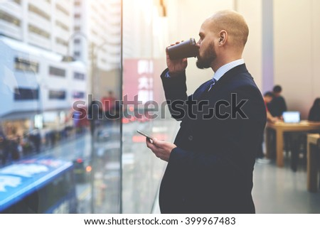 Man owner of successful enterprise is waiting for a all on mobile phone, while is watching on New York city view through office window. Male CEO with cell telephone in hand is thinking about job plan - stock photo