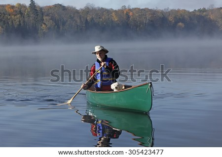 Man Paddling a Canoe on a Lake in Autumn with a Small White Dog in the Bow - Ontario, Canada - stock photo