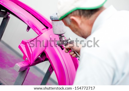 man painting a purple bumper of a car in special booth with airbrush - stock photo