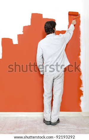 Man, painting a wall with orange paint and a paint roller - stock photo