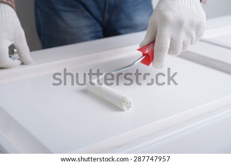 Man painting a wooden door using paint roller - stock photo