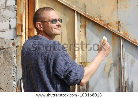 Man painting old rusted gate.  Ukraine - stock photo