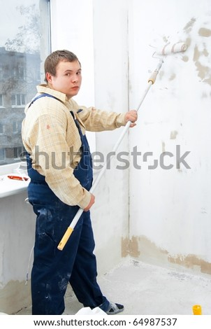 Man painting wall with roller. Indoor renovation theme - stock photo