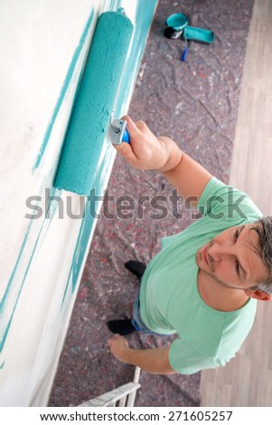 man painting white old wall - stock photo