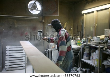 Man painting with spray paint gun in his home workshop - stock photo