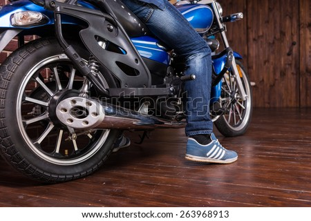 Man parking his motorbike indoors on a wooden floor with his foot on the ground, low angle view of the back tyre and foot - stock photo