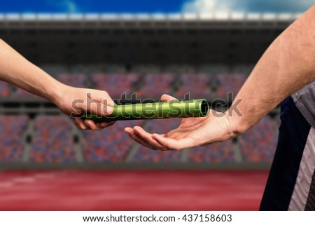Man passing the baton to partner on track against athletic field on a stadium - stock photo