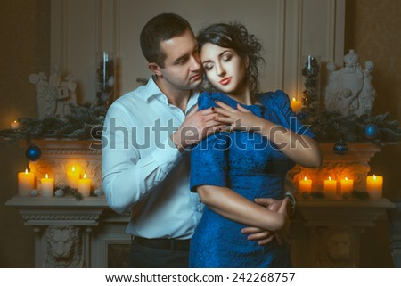 Man passionately hugged a woman in a room near the fireplace, around burning candles. - stock photo