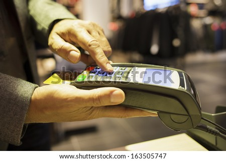 Man pay by credit card in clothing store - stock photo