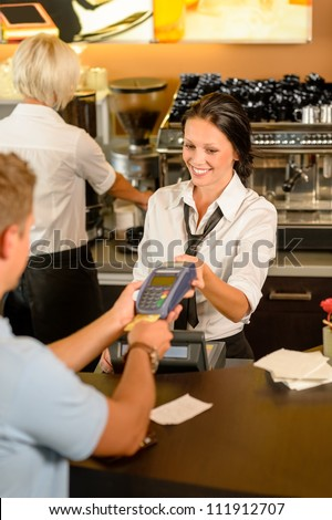 Man paying bill at cafe using card bill happy waitress - stock photo