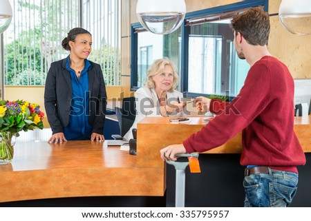 Man paying through credit card at hotel front desk - stock photo