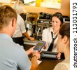 Man paying with credit card at cafe woman service cashier - stock photo