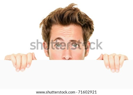 Man peaking showing blank empty white billboard sign surprised. Closeup of young man peeping over white banner edge. Isolated on white background. - stock photo