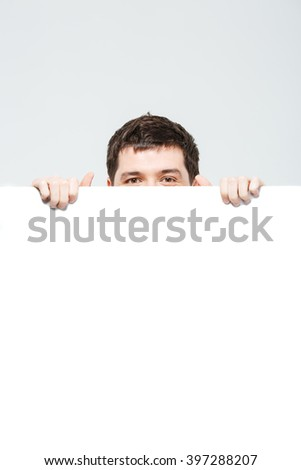 Man peeking from blank board isolated on a white background - stock photo