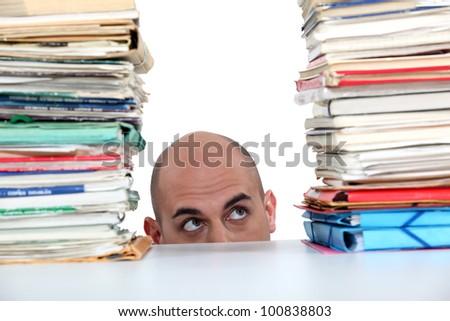 Man peering at files - stock photo