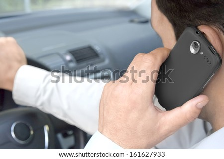 Man phones while driving a car - stock photo